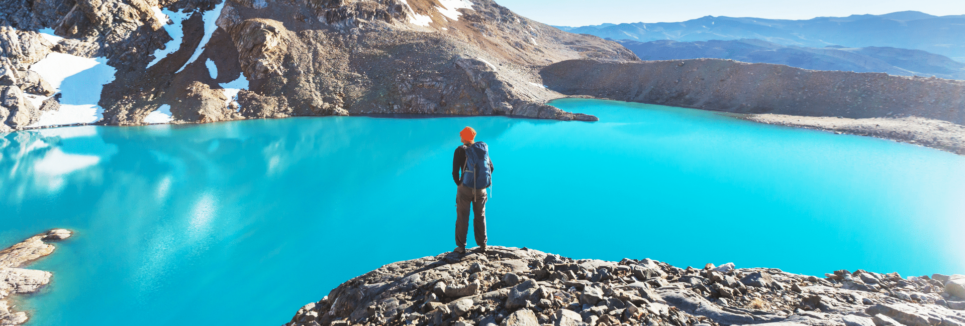 Hiker standing on a cliff overlooking a lake in Patagonia